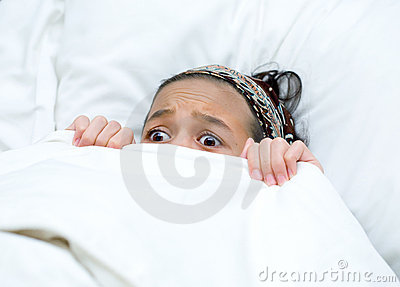 Child hiding behind blanket while watching movie