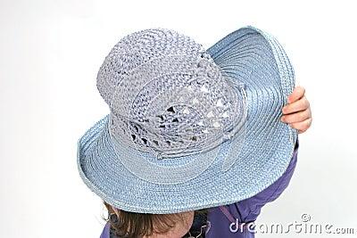 Child hiding under hat