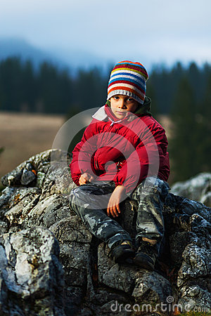 Child hiker sitting on cliff