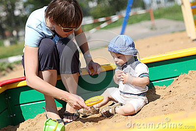 Child and his mother in sandbox