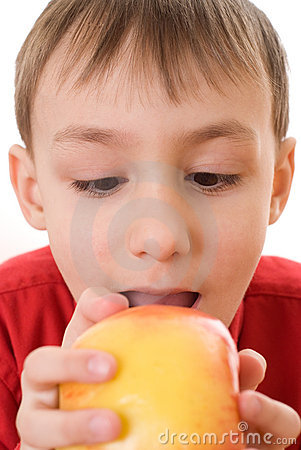 Child holding an apple and bites his