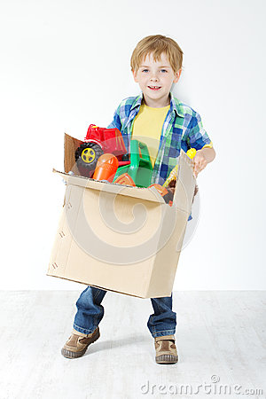 Child holding cardboard box packed with toys