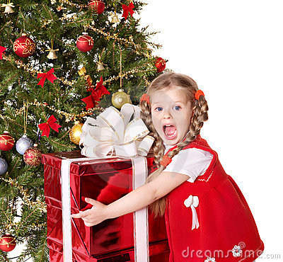 Child holding gift box by christmas tree.