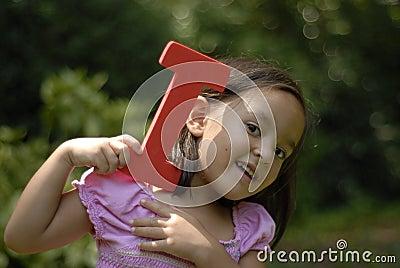 Child holding letter I