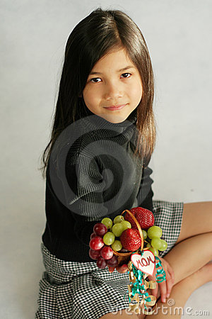 Child holding up fruit basket