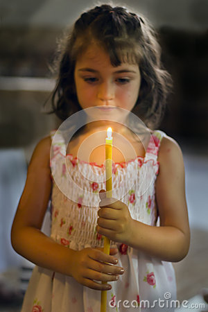 A child holds a candle in hands