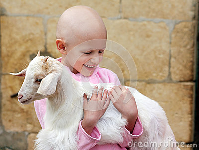 Child hugging goat
