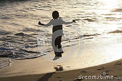 Child jumping on beach