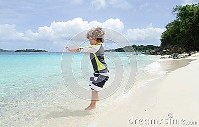 Child Jumping and having Fun on Tropical Beach near Ocean