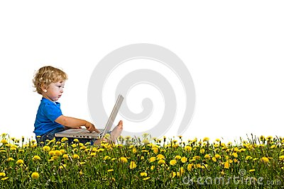 Child with laptop on a dandelion meadow