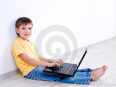 Child with laptop in empty room
