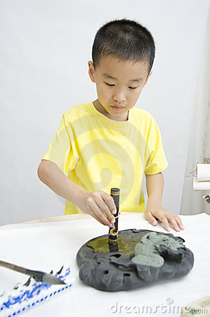 A child  learning Chinese Calligraphy