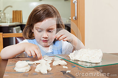 The child learns to mold dough figurines Stock Photo