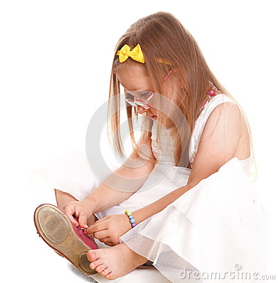 Child little girl tries to put on her shoes isolat