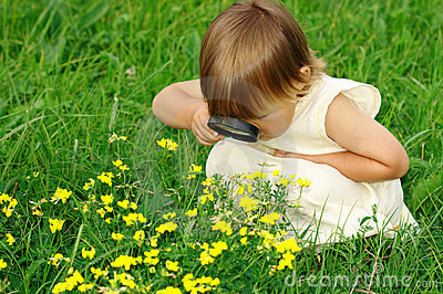 child looking at flowers through magnifying glass stock