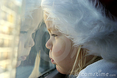 Child looking through window on very cold day