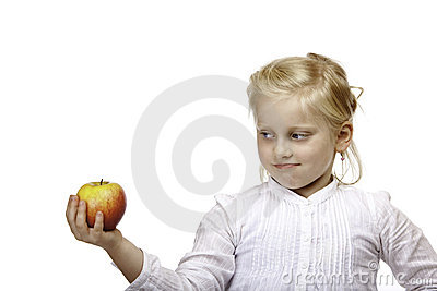 Child looks contemplative at healthy fruit (apple)