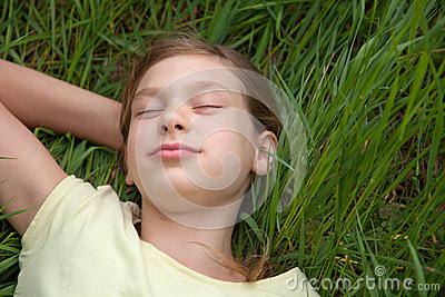 Child lying on a green meadow