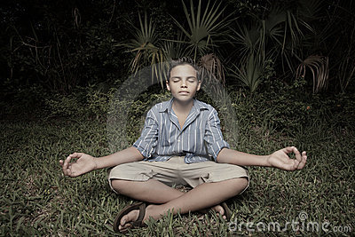 Child meditating on the grass