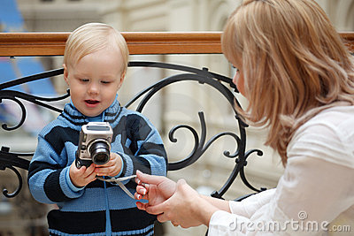 Child and mother. Boy examines photo with camera