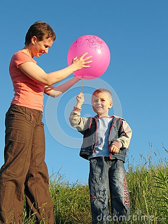 Child and mother play with ball