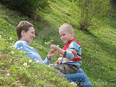 Child and mother play on grass