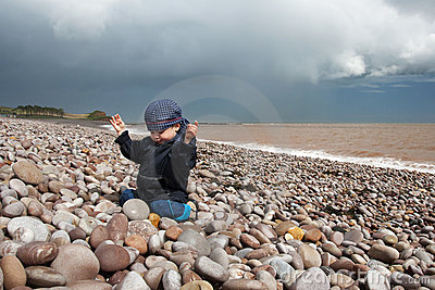 Child on a pebble beach in Devon, England