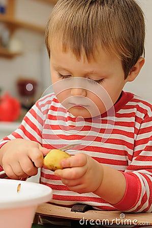 Child peeling potato