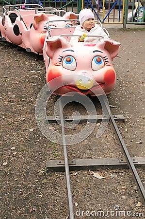 Child on piggy train in entertainment park