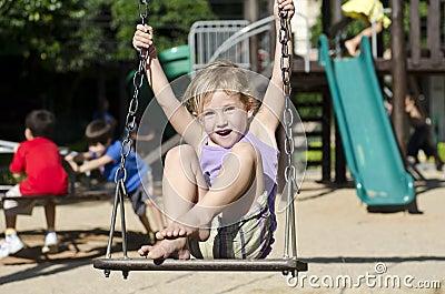 Child on the playground swinging