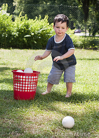 Child playing with balls in garden