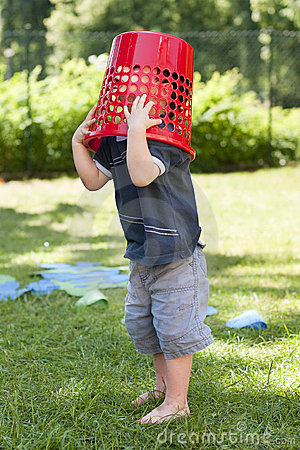 Child playing with basket in garden