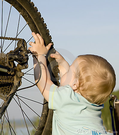 Child playing with bike wheel