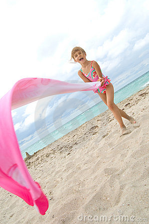 Child playing with a cloth at the beach