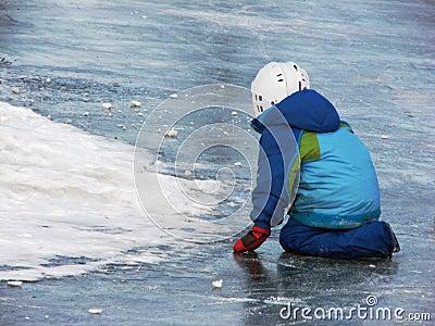 Child playing on frozen lake