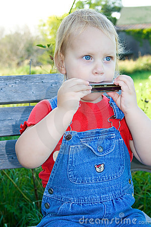 Child playing harmonica.