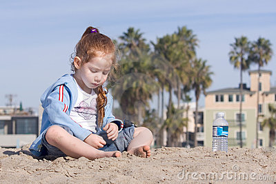 Child playing with sand on a beach