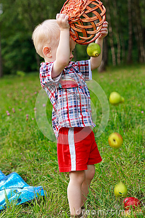 Child playing scattered of fruit with basket