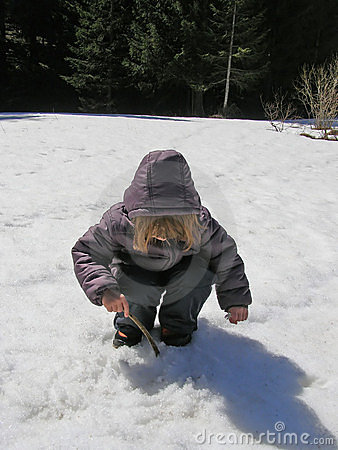 Child playing in snowy forest