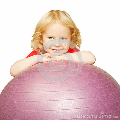 Child playing sports, smiling on fitball