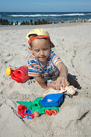 Child playint with toys on the beach
