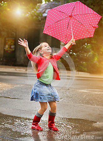 Child with polka dots umbrella wearing red rain boots Stock Photo