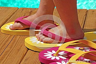 Child by pool wearing flipflops