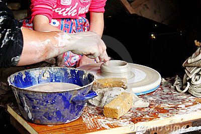 Child potter shaping clay in workshop
