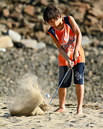 Child practice golf at the beach