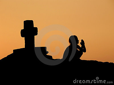 Child, prayer, cross in sunset