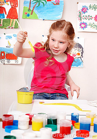 Child preschooler painting picture  in play room.