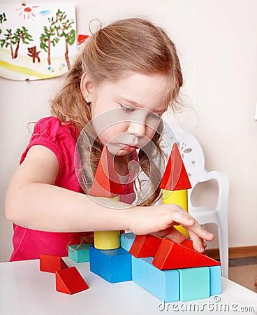 Child preschooler play wood block .