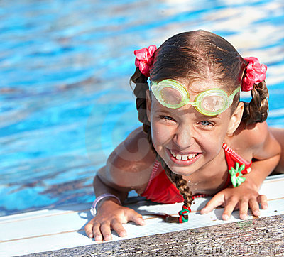 Child with protective goggles  in swimming pool.