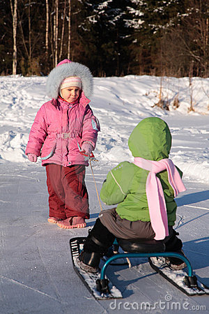 Child pulls another on snow scooter